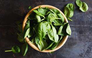 Vitamina K previne cheagurile de sânge și pierderile de sânge, dar prezintă multe alte beneficii pentru sănătate, regăsindu-se în legumele cu frunze verzi. Imagine cu un bol cu spanac, sursă de vitamina K