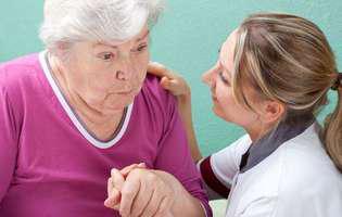 Tratează boala Alzheimer cu ginko biloba și alte remedii naturiste. Imagine cu femeie în vârstă afectată de boala Alzheimer și femeie medic care o susține