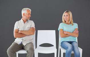 De ce soțul nu te mai iubește. Femeie și bărbat care stau supărați pe scaune la distanță unul de celălalt