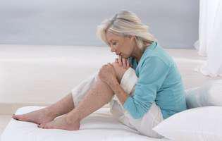 O femeie își masează genunchiul din cauza durerii provocate de osteoartrită