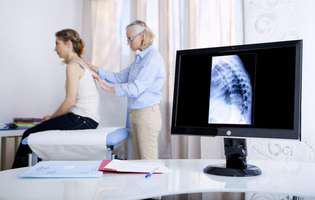 Un medic cercetează coloana vertebrală a unei paciente după ce i-a făcut o radiografie la coloană