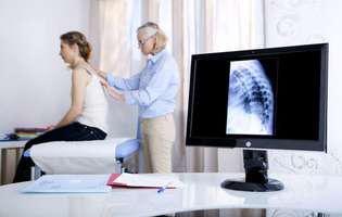 Scolioza. O tânără este consultată de un medic din cauza unei deviații la coloana vertebrală