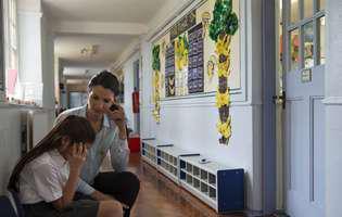Bullying-ul la școală. Eleva suparata alaturi de mama ei pe holul unei scoli