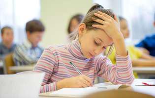 elevii vor sta cu două ore oe zi mai mult la școală. Fetiță obosită în bancă într-o clasă cu elevi