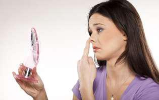 Fractura nazală reprezintă un traumatism al unui os al nasului care poate necesita intervenția medicului. Imagine cu femeie care își examinează nasul în oglindă