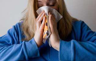 Sinuzita acută - afecțiune care poate fi tratată clasic sau naturist. Imagine cu femeie care își suflă nasul și care suferă de sinuzită acută