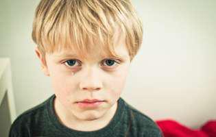 Copil care plânge pentru ca nu vrea să meargă la grădiniță