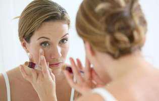 Pungile de sub ochi reprezintă o afecțiune care poate fi tratată cu remedii naturiste sau convenționale. Imagine cu femeie care își examinează pungile de sub ochi