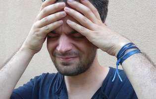 Durerea de cap cronică poate afecta sever calitatea vieții unei persoane. Imagine cu persoană care suferă de durere de cap cronică
