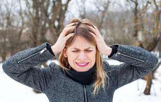 Durerea de cap declanșată de efortul fizic poate fi prevenită sau tratată prin medicație. Imagine cu femeie care suferă de durere de cap ca urmare a efortului fizic