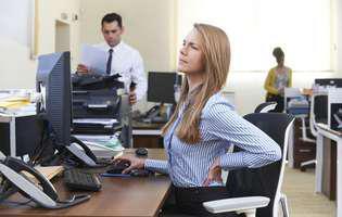 Durerile de spate pot apărea din cauza statului prea mult la birou