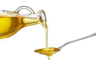 Cele mai sănătoase uleiuri. Ulei turnat dintr-o sticlă într-o linguriță