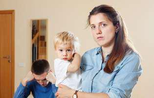 Probleme în cuplu după nașterea copilului. Femeie tristă cu un bebeluș în brațe. În spatele ei stă un bărbat cu capul în mâini
