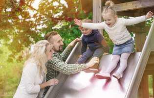 Doi copii se dau pe tobogan supravegheați de părinți