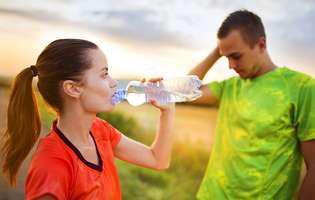 Efectele negative ale sportului. Femeie și bărbat în aer liber. Ea bea o băutură energizantă