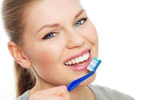 Cum previi gingivita prin metode naturale: femeie frumoasă care se spală pe dinți.