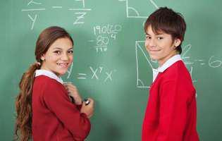 Uniforma școlară. Doi copii la tablă care poartă uniformă școlară roșie