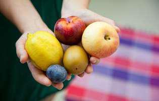 Alimente care previn bolile cardiovasculare recomandate de dr. farmacist Ovidiu Bojor: fructe. O mână de femeie ține un măr, o lămâie, o prună și o piersică