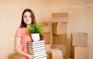 Ce trebuie să știe un tânăr înainte de a se muta singur: să-și organizeze resursele. Fată cu cărți, pachete și plantă se mută la cămin