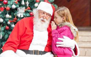 Poezii pentru Moș Crăciun. Ce poezii să-i spună Moșului în seara de Ajun. Fetiță șoptind ceva Moșului