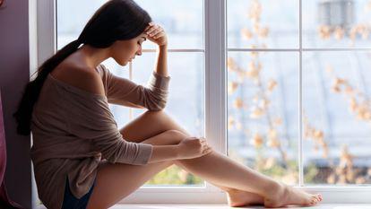 femeie care se uita pe fereastra