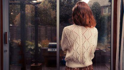 femeie care priveste ploaia