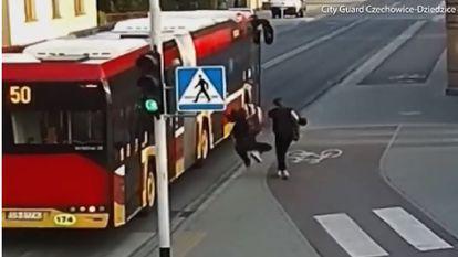 O tânără a fost la un pas de a fi strivită de un autobuz după ce prietena ei a împins-o pe stradă în glumă - Tanara cade foarte aproape de un autobuz rosu