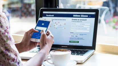 Laptop şi telefon pe care este deschisă aplicaţia Facebook