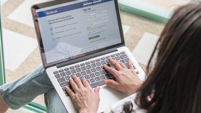 o femeie cu laptopul in brate se uita pe facebook