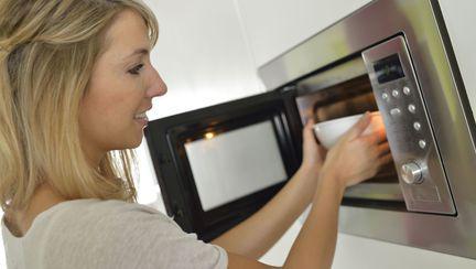 femeie care foloseste cuptorul cu microunde