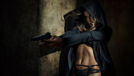femeie care tine un pistol