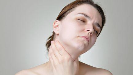 femeie care isi maseaza tiroida