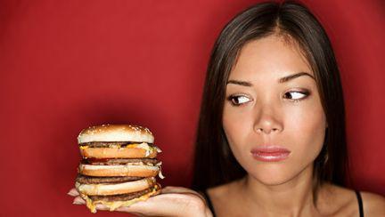 femeie cu un burger in mana