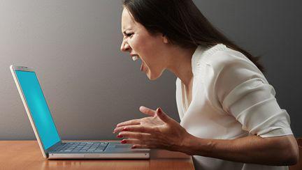 Femeie care se enervează î fața calculatorului