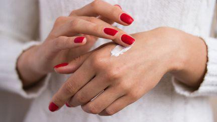 femeie care se da cu crema de maini
