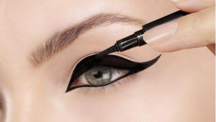 Fata care se machiaza cu eyeliner