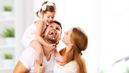 O fetiță cu tatăl și mama ei, râzând
