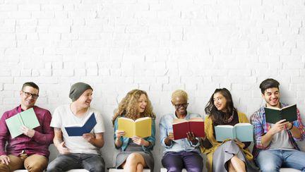 Tineri care au carti in mana si citesc