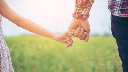 Am cancer - cuvintele care mi-au schimbat viața - fetita si tatal se tin de mana pe un camp cu iarba verde