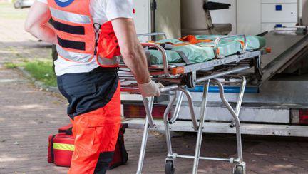 medic care împinge targa în ambulanță