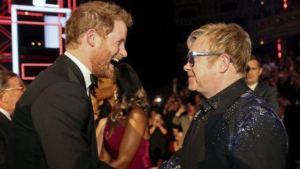 Prințul Harry și Elton John ce își dau mâna