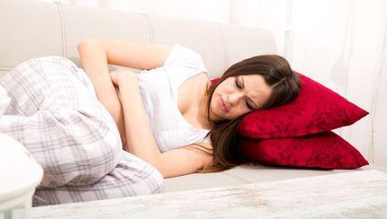 o tânără stă întinsă pe canapea, având dureri mentruale