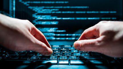 hacker care foloseste un laptop pentru un atac cibernetic