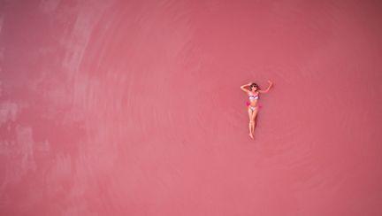 femeie intinsa pe un lac cu apa roz