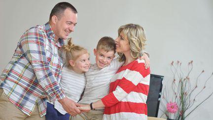 Familie cu doi copii care se îmbrățișează