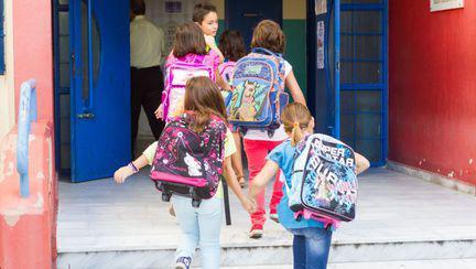 copii cu ghizdanele in spate care alearga spre scoala