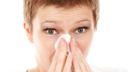 femeie care-si sufla nasul