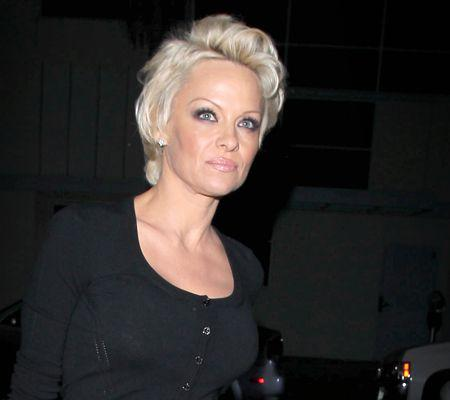 Pamela Anderson gets cozy with a male companion at Crossroads