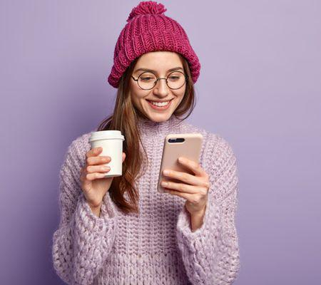 young-brunette-woman-wearing-purple-sweater-holding-cup-coffee_273609-22291