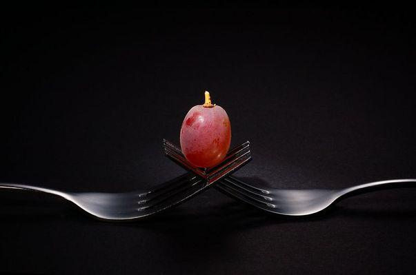 Single red grape sitting centred on top of two intertwined stainless steel forks, black background